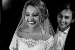 B&W smiling elegant blonde bride in vintage white dress smiling before the wedding