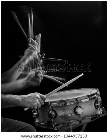 B&W stroboscopic action shot of a drummer hitting a snare drum. #1044957253