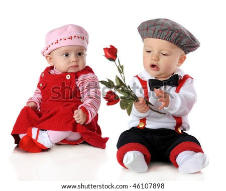 Babies dressed up for Valentine's Day.  The boy holds long stemmed roses while the girl looks on.
