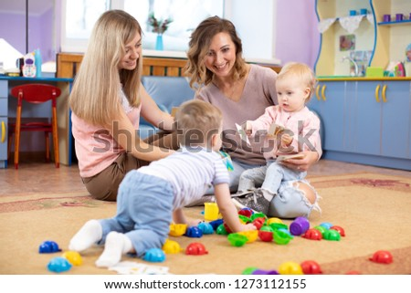 Babies play and their moms communicate in playroom
