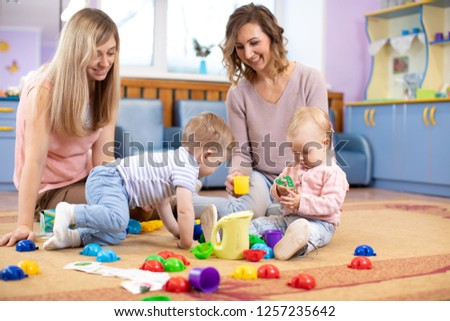 Babies toddlers crawling and having fun on floor in nursery. Mothers play with children in day care centre.