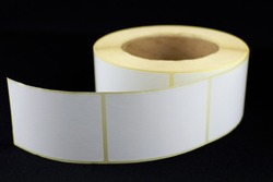 Babina of self-adhesive stickers on a black background. Self-adhesive white label roller for printing or manufacturing.