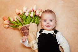 baby, a little gentleman lies on a bed with a bouquet of tulips, a gift to mom on a holiday