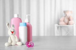Baby accessories and toy on table against light background. Space for text