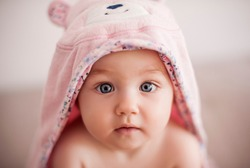 Baby after bathing. Baby girl is in pink  teddy bear towel.