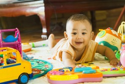 Baby age 6 months learning and playing developmental toys indoors.