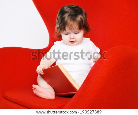 Baby and book on red chair