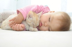 Baby and cat sleeping together on white sheet, kitten and baby girl childhood friendship