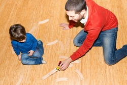 Baby and father playing with train on the floor