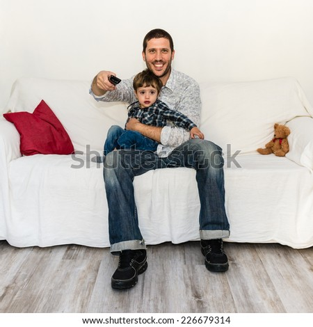 Baby and father watching tv on a white sofa