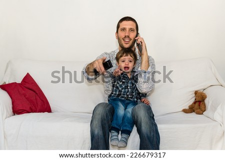 Baby and father watching tv on a white sofa while baby is crying