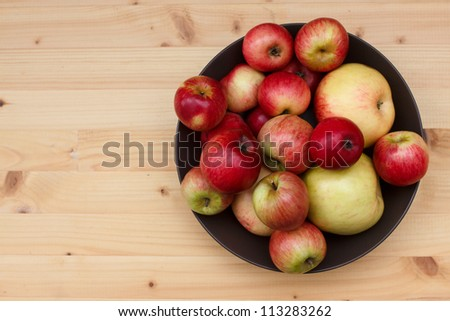 Baby and full size apples in a dish on a pine table