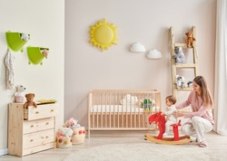 Baby and her mom in the room, decorative interior style with wooden cribbed pink chair toy and stair decor.