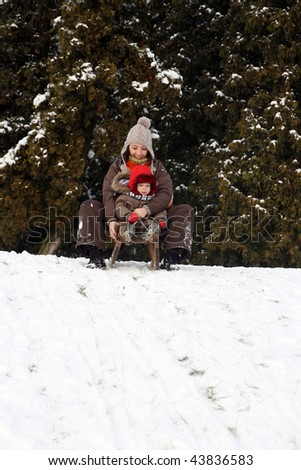 Baby and mom sledding in cold winter day