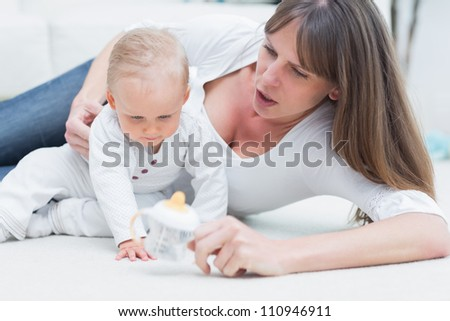 Baby and mother sitting on the floor in living room