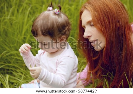 baby and redhead mother outdoor grass playing park together - stock photo
