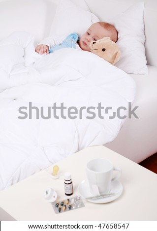 Baby and teddybear lying in bed with cup of tea and medicine