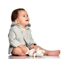 Baby and toy bunny isolated. Barefoot infant child in knitted wear sitting on white floor studio background. Kid with favorite plaything looking aside. Innocence and Happy Easter concept