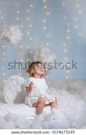 baby angel sitting in the clouds looking up