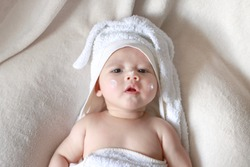 Baby applying lotion cream on face after bathing for protect skin. Newborn boy wrap by rabbit white towel drying after shower at home