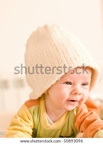 baby at six months crawling covered with hat