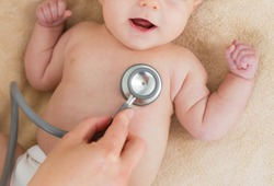 Baby at the doctor getting breath check up with stethoscope