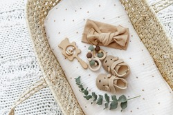 Baby basket with newborn items, booties and toys. Still life of child products. Newborn background. Minimalist style photography of baby shower, pregnancy announcement.