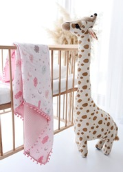 baby blanket and toy giraffe hanging in the crib.