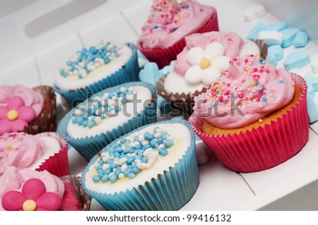 baby blue and pink cupcakes with flowers and hearts