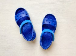 Baby blue rubber sandals on a white background.  Comfortable kids massage beach sandals.  Top view, isolate.