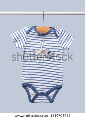 Baby bodysuit hanging on a clothesline isolated on blue background/ Close-up. #1514706485