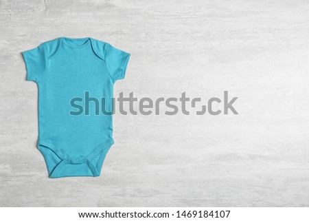 Baby bodysuit on wooden background, top view. Space for text #1469184107