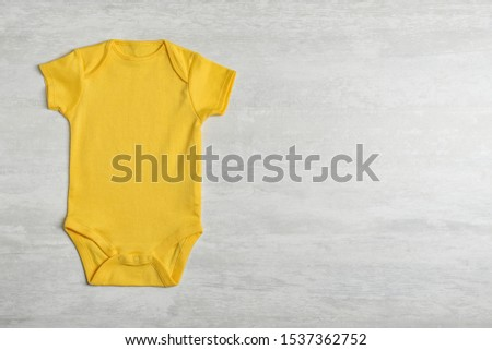 Baby bodysuit on wooden background, top view. Space for text #1537362752