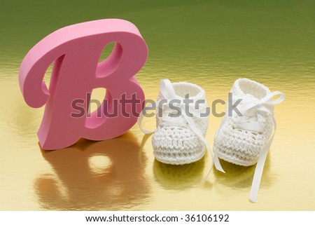 Baby booties with a pink letter b on a shiny, baby booties