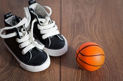 Baby boots on wood floor and a basketball