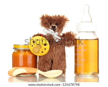 Baby bottle with fresh juice, puree and teddy bear isolated on white