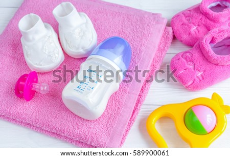 baby bottle with milk and towel on wooden background
