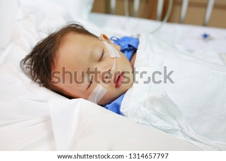 Baby boy age about 1 year old sleeping on patient bed with getting oxygen via nasal prongs to assure oxygen saturation. Intensive care at hospital. Respiratory support.