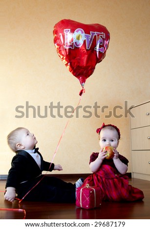 baby boy and baby girl well-dressed playing together
