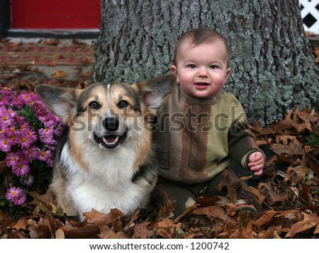 baby boy and dog sitting in leaves