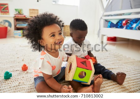 baby boy and girl playing with...