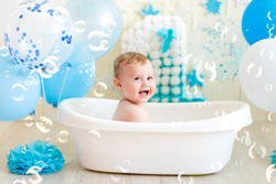 baby boy celebrates birthday 1 year in a bath with balloons, bathing the baby in a bath with foam, soap bubbles and blue balloons