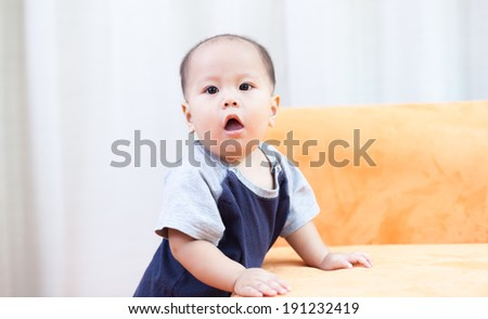 Baby boy.child Asian., And played on the orange sofa.