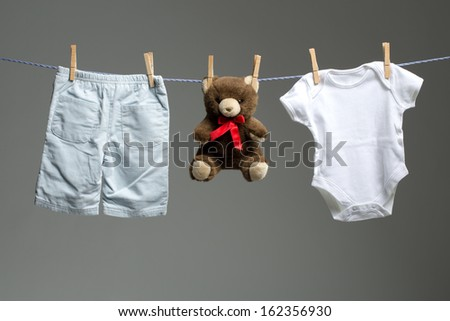 20455d330 Baby boy clothes and white toy bear on a clothesline Images and ...