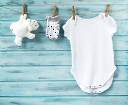 Baby boy clothes and white toy bear on a clothesline