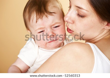 baby boy crying in mothers arm; closeup faces