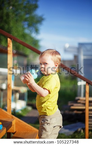Baby boy drinking juice outdoors