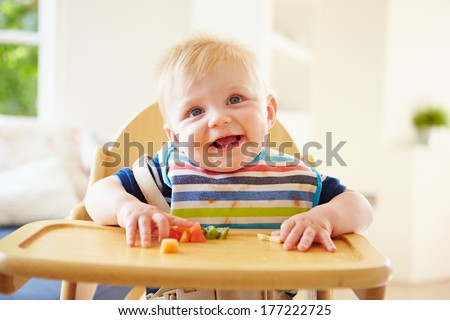 Baby Boy Eating Fruit In High Chair Stock foto ©