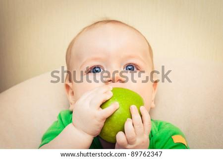 Baby boy eating green apple - stock photo