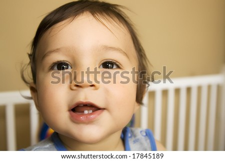 Baby boy - eleven months old - smiling while reaching out of his bed - stock photo